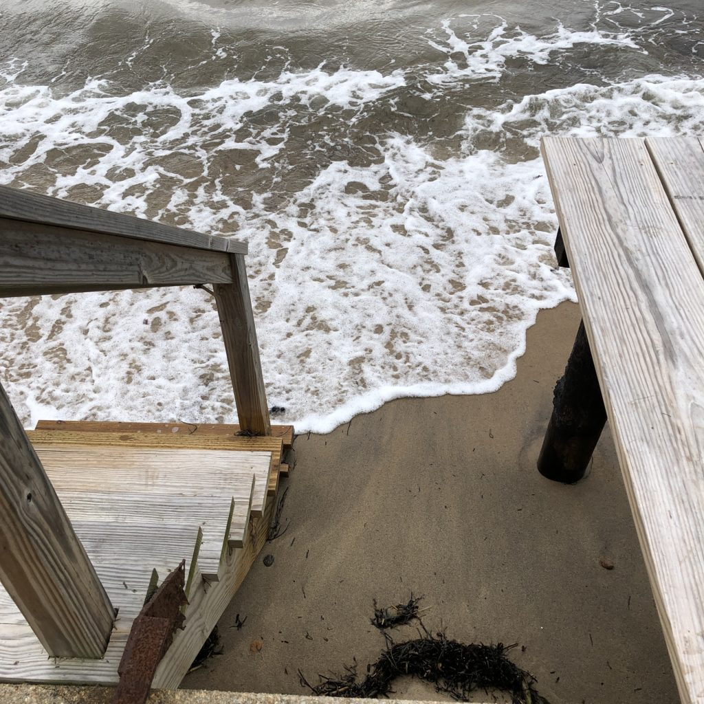 wooden steps with ocean waves at foot of stairs